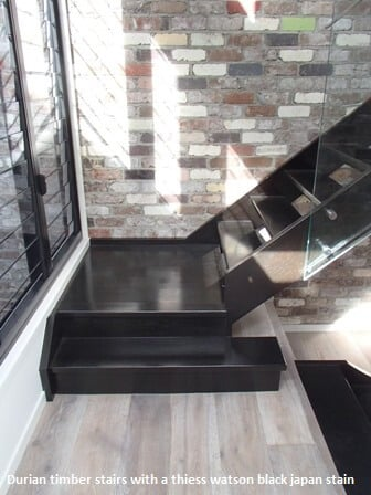 Black stairs with brick feature wall